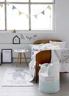 Dormitorio infantil niño estilo nórdico. Cama de madera con colcha, sábanas y cojines en tonos blancos, verde agua con ilustraciones negras