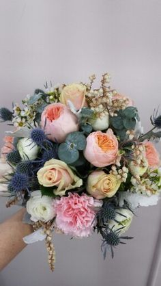 Gathered style bouquet of garden roses ,seaholly,ranucs and andromeda and blugum foliage.