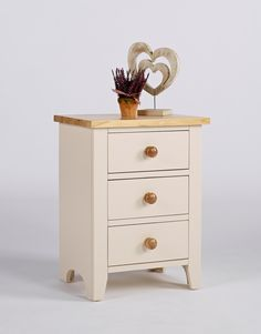 New England Painted Three Drawer Bedside Cabinet This is a beautiful bedside cabinet  Clean fresh lines and lightly painted in ivory  It has three deep drawers The drawers are tongue and groove With contrasting wooden knob handles The top is solid ash that has been lightly lacquered This is a satin finish which is resilient and serves to protect the natural beauty of the ash The frames are solid pine With high quality MDF panelling Finished in a knock resistant paint in ivory