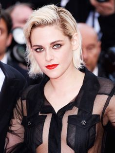 Kristen Stewart pairs her platinum locks with a bright red lip.