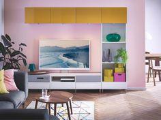 Un salón de color rosa con muebles abiertos y cerrados BESTÅ para guardar discos y vídeos, en colores amarillo y blanco brillantes