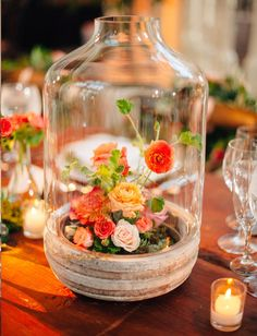 Terrariums are an excellent way to display florals in a cooler outdoor environment. Add some LED lights and you have a glowing centerpiece. The Knot.