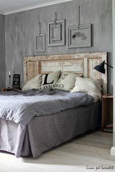 Des cadres vides suspendus à des chaînes et peints de la couleur du mur, des caisses en bois comme chevets et surtout cette porte ancienne faisant office de tête de lit. photos par Lina på Landet.