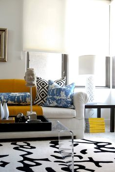 white, black, caramel, blue, yellow - lucite table, rug, pillows. love.