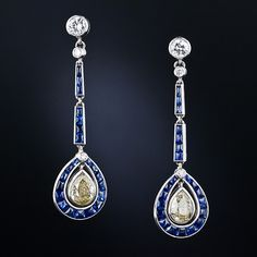 Intriguingly beautiful pair of Art Deco drop earrings - circa 1925. A slender, articulated line of buff-top sapphires suspend a matching teardrop shaped frame, each of which dangles with a sparkling, intense greenish-yellow old mine pear-shaped diamond, weighing about .80 carats each. The ear drops are suspended from a sparkling round brilliant-cut diamond ear stud, which was evidently added at a later date.