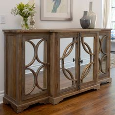 Add this wood contemporary sideboard to your home for added style and function. The mirrors provide a lovely accent to the natural-wood finish, and the 79-inch top combined with the interior shelves offer ample storage for decorations and supplies.