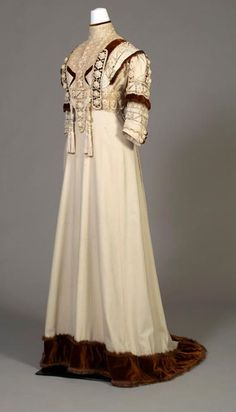 1910 American dress of ivory wool trimmed with Irish lace, brown velvet, and fur.