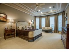 Luxurious master bedroom // Tray ceiling, wall of windows, tufted bed