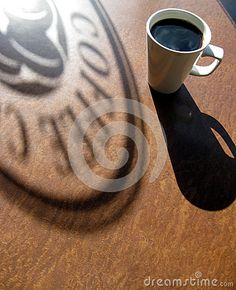 Window sign and coffee mug shadows on the cafe table
