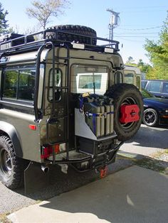 Defender 110 rear swinging arm with chainsaw gas (red) and additional diesel. As rear winch and a pelican case integrated.