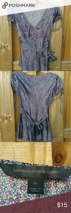 Express Silky Blue & Purple Floral V-Neck Shirt Adorable silky v-neck short sleeved dress shirt with cute tie details at both the shoulders and in back. Tiny blue and purple flowers adorn this shirt pattern. Size M, 95% silk, 5% spandex. Hand wash cold. Express Tops Blouses