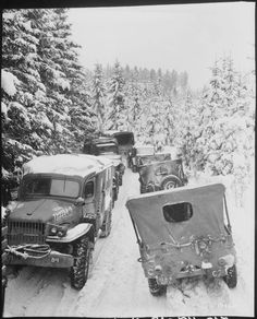 Deep snow banks on a narrow road halt military traffic as elements of Company C 312th Medical Battalion 87th Infantry Division and 307th Airborne Engineer Battalion 82nd Airborne Division meet in the woods of Wallerode Belgium January 1945.