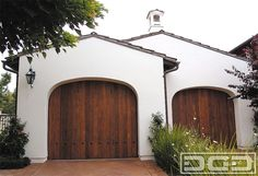 Finished in select tight knot cedar, these custom wood garage doors in a Spanish Colonial style ensures the architectural continuity throughout the home's design. Large iron clavo heads enhance the custom garage door's Spanish Colonial design. Hand stained in a variation of tints give these doors a rustic appearance that fuses well with the terra …