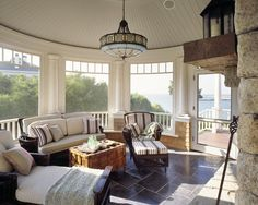 Different angle of screened porch:  love the screens with transoms; stone fireplace; turret; pine mantle; rattan furniture; bluestone floors; ceiling light is growing on me