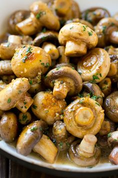 Garlic mushrooms in an herb and butter sauce in a frying pan.