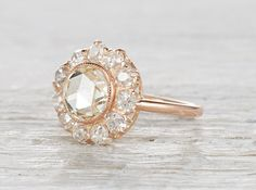 Vintage Edwardian rose gold engagement ring centered with a 1.20 carat yellow rose cut diamond. Accented with 11 old European cut diamonds. Circa 1915 This feminine ring is sweet and sparkly and the rose cut diamond adds interest to the traditional Edwardian cluster setting.