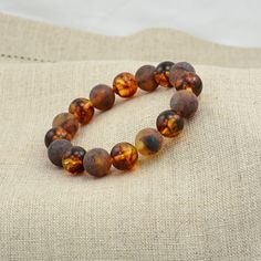 Baltic amber healing bracelet made of round cut unpolished and polished dark cognac Baltic amber beads