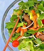 """This beef salad recipe offers a feast of flavors and textures with every bite! This salad is based on the famous """"Waterfall Beef"""" dish in Thailand, so called because of the splashing sound of juices falling on a hot grill. The beef is lightly grilled or oven-broiled, sliced thinly, then served with a mixture of salad greens and fresh papaya along with a special Thai dressing. Serve as the main course for a nutritious and oh-so-delicious dinner that's naturally high in protein and low in…"""