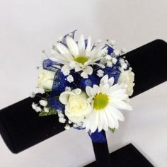 Wrist corsage of pretty white daisies & white spray roses with a sparkly royal blue bow.