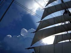 The Sea Cloud's distinctive square sails billow against a cloud-filled sky. IRT Photo by R. Fisher