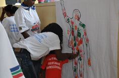 Child painting a Mandela fresco by United Nations Information Centres, via Flickr