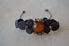 An earthy, mesmerizing macrame bracelet featuring a translucent onyx stone in the center, surrounded by intricately knotted spirals in dark brown