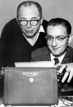 """BILLY WILDER and frequent screenwriter partner, I.A.L. DIAMOND.  """"Izzy"""" is seated at the typewriter, with Wilder standing, as usual. Wilder liked to """"think on his feet"""" and was a notorious pacer. Wilder & Diamond wrote 17 films together, including: SOME LIKE IT HOT, THE APARTMENT, LOVE IN THE AFTERNOON, IRMA LA DOUCE"""