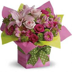 Quite possibly the prettiest pink present ever! A fantastic array of pink flowers in a hot pink gift box is contrasted brilliantly with bright green blossoms and a bow!