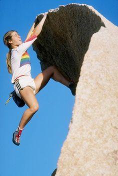 Lynn Hill free climbing a rock during the day