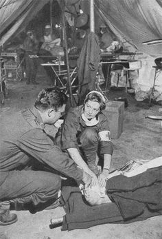 O.R. ward tent. Foreground a Nurse and a Medical Officer treat a patient's foot, while Surgeons in the background are operating another patient lying on a litter