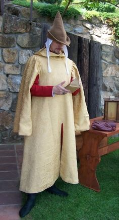 Gardcorps       initially man's garment was used in 13th and 14th century as a practical kind of cloak. Below brocade garment (pattern) lined by thick wool cloth man wears red cotte and green hose. The head is covered by white linen coif and brown woolen hat. Half of 14th century.