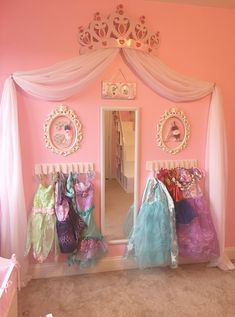 Princess dress up storage diy. Cheap and super easy! Frees space by putting the dresses on the wall. Spray painted wood boards and clothes pins then hot glued the clothes pins to the wood board and hung on the wall. The kids can add and remove the dresses with ease!
