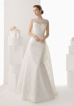 A beautiful, lace wedding dress with a flattering, slim A-line silhouette belted at the natural waist and with an extended chapel-length panel train. The high, sleeveless, illusion lace neckline is complemented with a high lace illusion back and button-loop closure.
