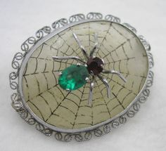 Deco frosted camphor glass pin with spider, emerald paste body