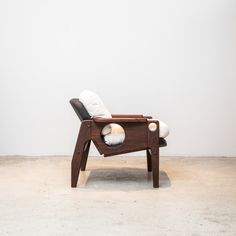 """One of the last pieces Sergio Rodrigues designed, in 2013, the joyous """"Tete"""" armchair boasts Rodrigues' signature circle cutouts, and is made from solid Brazilian native Freijó wood and fabric and leather upholstery."""