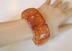 This stunning #vintage stretch bangle bracelet features rich amber lucite chunky links with the look and feel of genuine amber.  The bracelet is one and one-fourth inches wi... #jewelry