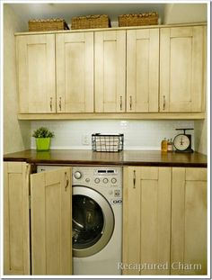 Concealed laundry machines in peek-a-boo cabinets.