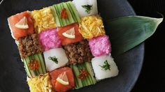 Recipe with video instructions: How to make a Mosaic Block Sushi. Ingredients: 280 cc rice, 260 cc water, 4 tsp sake, (sushi rice seasonings), 40 cc rice vinegar, 2 tsp sugar, 1 tsp salt, (sushi fillings and toppings), 3 sheets nori, cut in half, 2 slices smoked salmon, 3 thinly sliced lemon, 1/2 cucumber, thinly sliced, ikura (salmon roe), sakura denbu (pink fish flakes), 1 small fillet of squid (sashimi quality), 1 pirella leaf, cut into thin strips, (seasoned ground chicken), vegetabl...