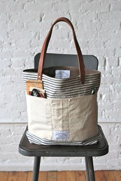1950s era Ticking Fabric Tote Bag. Bag measures approximately 15 in wide, 13 in tall, 4.5 in deep. Strap drop approximately 9 in.