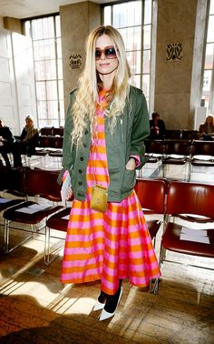 Laura Bailey wears a pink and orange striped dress with an army jacket, black tights and white pumps.
