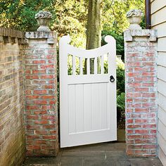 picket arbor gate  fencing with brick or stone posts.... Updated Colonial Gate - Choose the Perfect Garden Gate | Southern Living