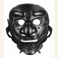 Full-face mask  Date: 1615-1650  Medium: Iron and lacquer. Asian Art Museum. This full-face mask has embossed eyebrows and eyelids. It is fitted with flanges running from the ears down each cheek to protect the helmet cord (yadome). The mask is pierced along its top edge to allow the attachment of a fabric hood, which, like the hoods of many full-face masks, is now lost.