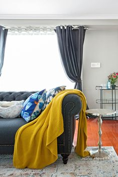 Chesterfield sofa in navy fabric, which yellow throw and various cushions