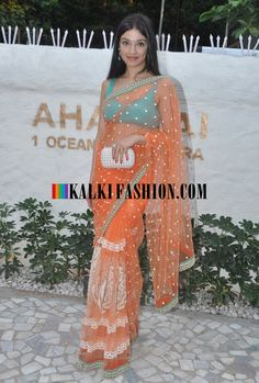 http://www.kalkifashion.com/   A celebrity in orange netted embroiderer  saree with contrast blue blouse at Alvira Khan and Ashley Rebello,s new store launched named Ahakzai