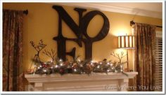 Wooden letters, painted, gilded, yarn-covered, decorated any way that strikes your fancy, glued together and placed on the mantle behind a lighted garland.
