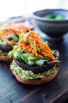 Asian-style, grilled, vegan portobello mushroom burger is full of delicious umami flavor! It's lathered with Asian-style Guacamole, topped with a cool cucumber ribbon salad and crunchy carrot slaw. Healthy, delicious and really satisfying. Vegan Mushroom Burger, Portobello Mushroom Burger, Grilled Portobello, Asian Slaw Salad, Crostini, Vegetarian Recipes, Healthy Recipes, Vegetarian Barbecue, Gastronomia