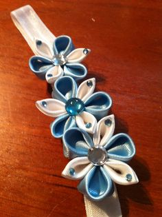 Kanzashi flowers on an elastic headband in pale blue and white satin ribbon.