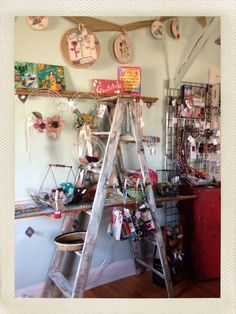 Ladder display in gift shop! Such cool and inexpensive DIY shelving-sourced it at Habitat ReStore :) #ladderdisplay #Art2Heart #retaildisplay #havetogetridofthegrids