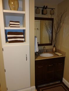 Tall built-in cabinet designed to store bathroom stuff and hide up-pumping equipment in the base.