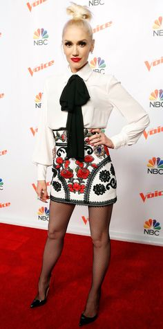 Gwen Stefani brought her punk-rock 'tude to The Voice press junket event with a tie-neck blouse (aka the hottest top of the sesason) tucked into floral embroidered red-black-white mini, complete with black fishnets and two-tone pumps.